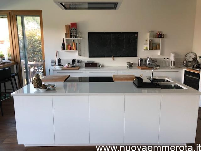 Cucina ad isola e mobile ad angolo a parete con mensole di design a muro