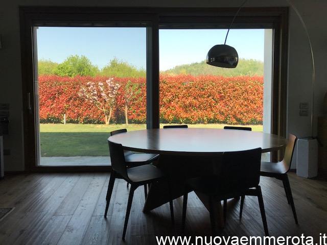 Tavolo soggiorno rotondo davanti vetrata sul giardino