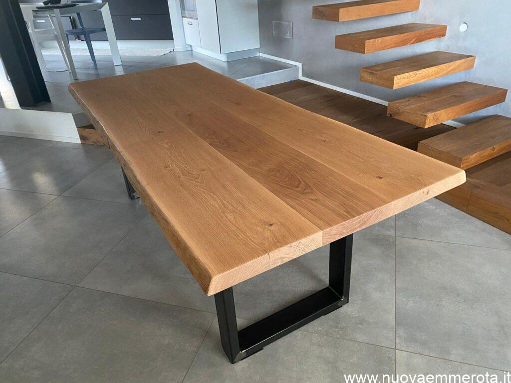 Tavolo su misura con base in metallo nero.