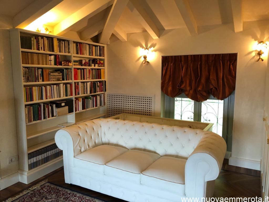 Zona lettura con libreria bianca e divano.