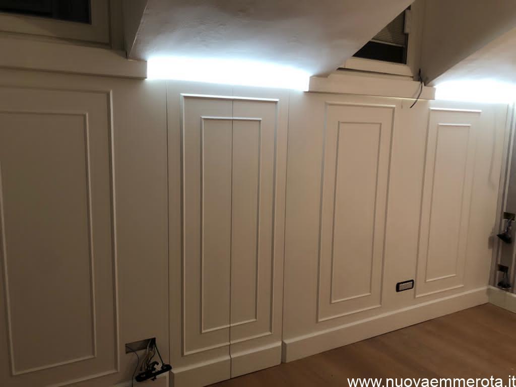 Boiserie bianca in stile classico in sala mansardata