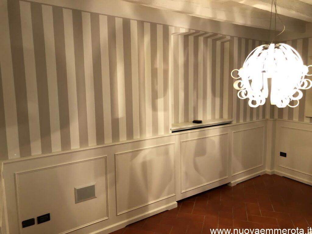 Boiserie bianca in stile classico in abbinamento a pavimento marrone.