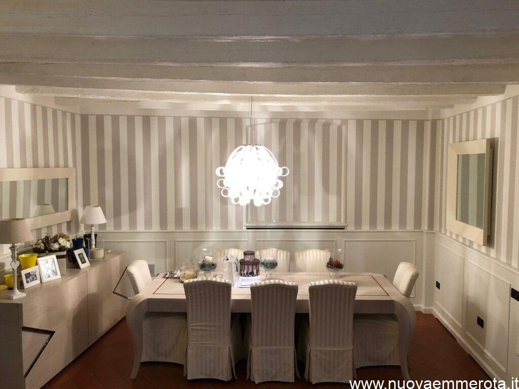 Boiserie bianca in stile classico con tavolo rettangolare e sedie.