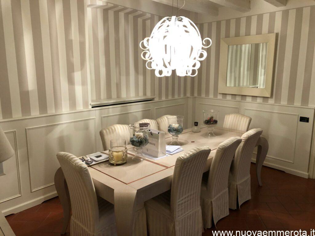 Boiserie bianca in stile classico nella sala da pranzo con tavolo bianco e sedie