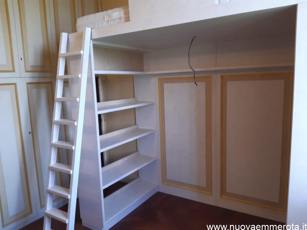 Cameretta con letto su struttura in legno e libreria con boiserie.