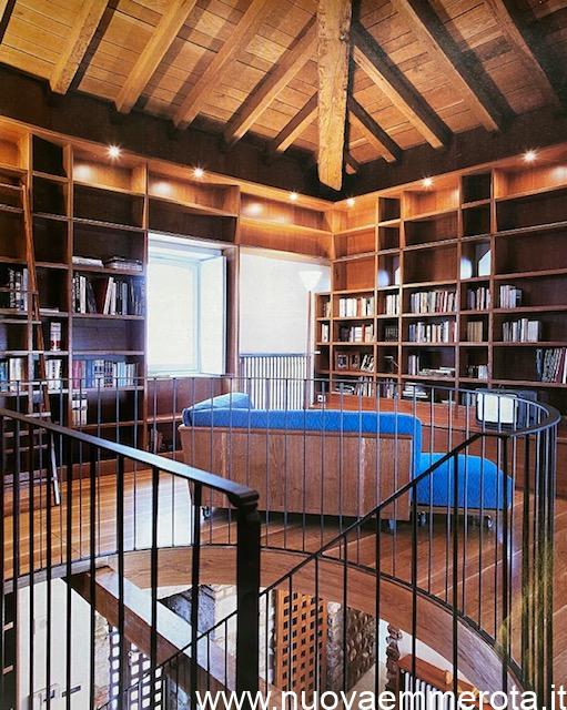 Libreria di design a tutta altezza con scala per scaffali alti.