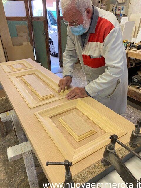 Lavorazione cornici elegante porta in legno con cornici nel telaio