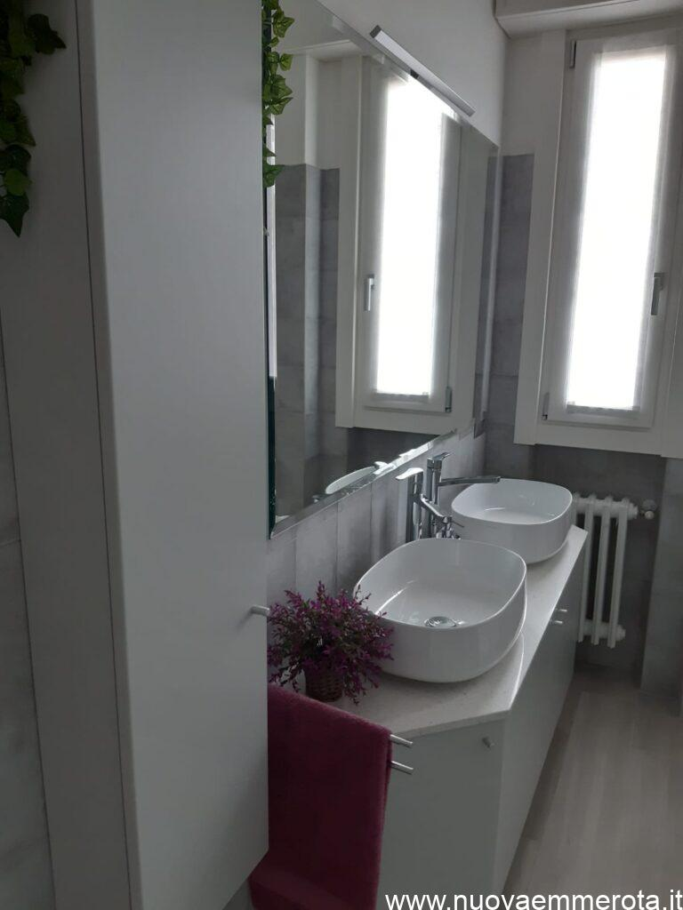Mobile bagno sagomato con armadietto porta oggetti.