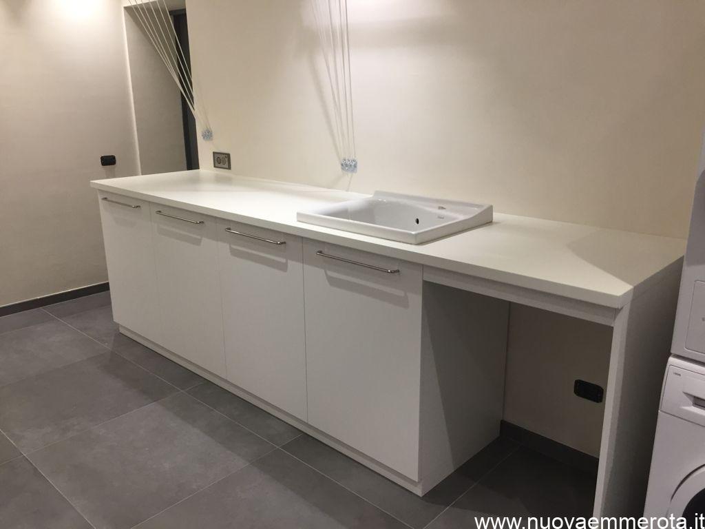 Mobile lavanderia con lavabo, cassettoni e spazio per lavatrice.