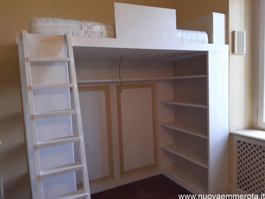Arredo cameretta con struttura letto con boiserie e libreria.