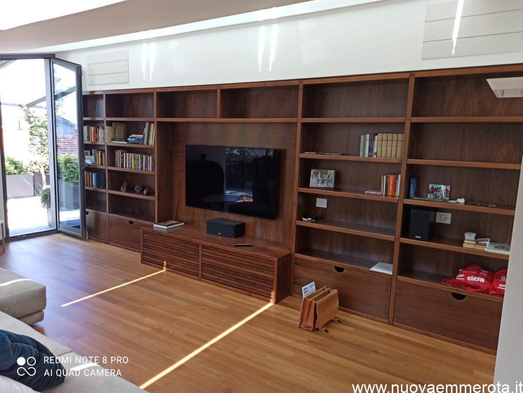 Libreria a parete in noce con quattro cassettoni e parti a giorno.