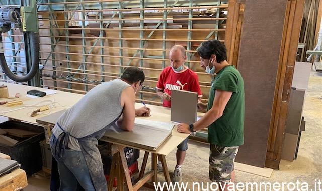 tre falegnami in riunione prima di iniziare a lavorare il legno in falegnameria.