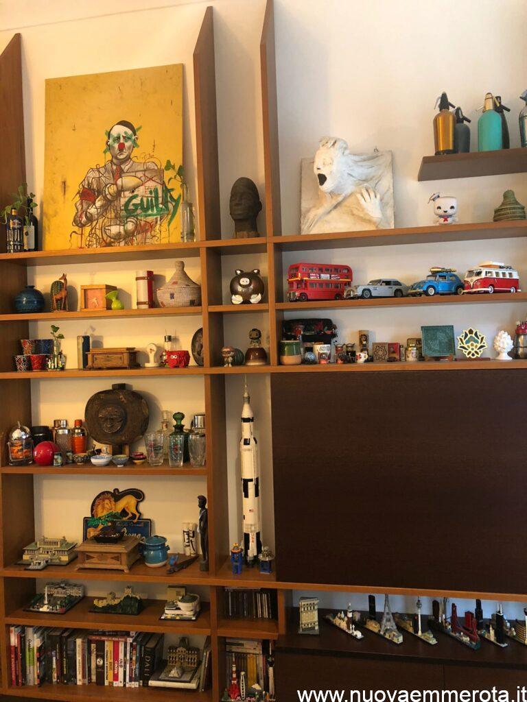 Libreria in teak del Siam con oggetti artistici e modellini lego.