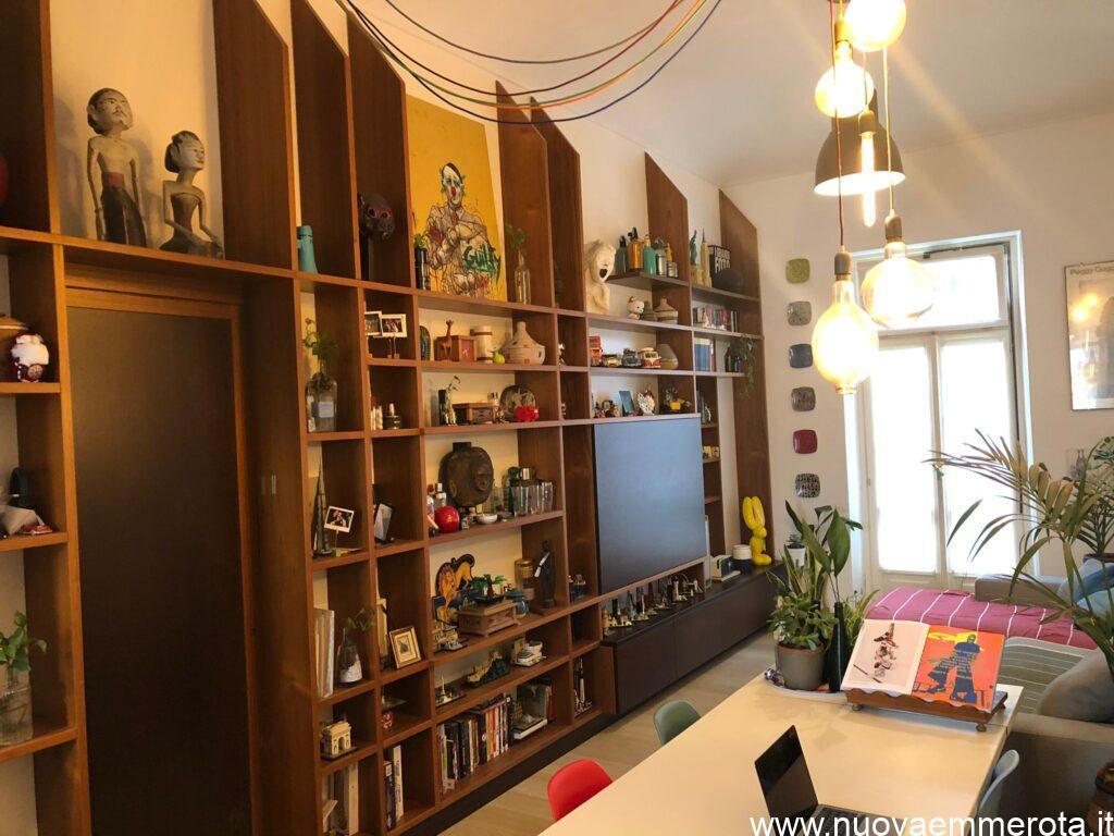 Libreria in teak del Siam con oggetti artistici ed imbotte intorno alla porta che porta nella zona notte..