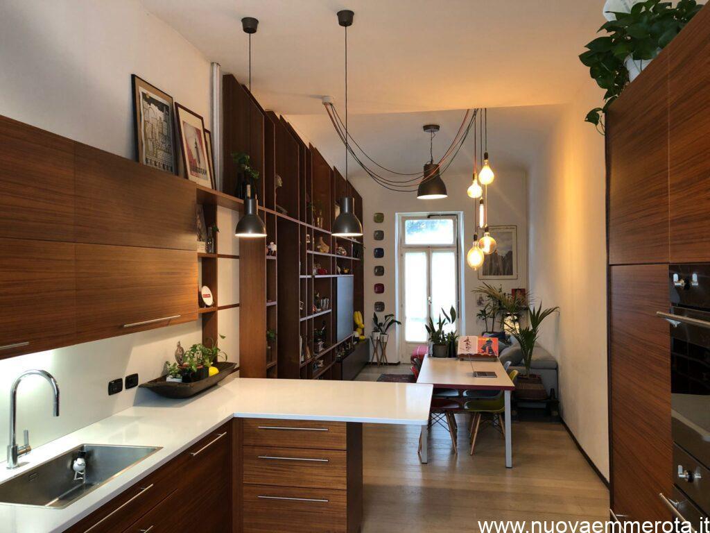 Open space zona living con cucina e libreria in legno teak.