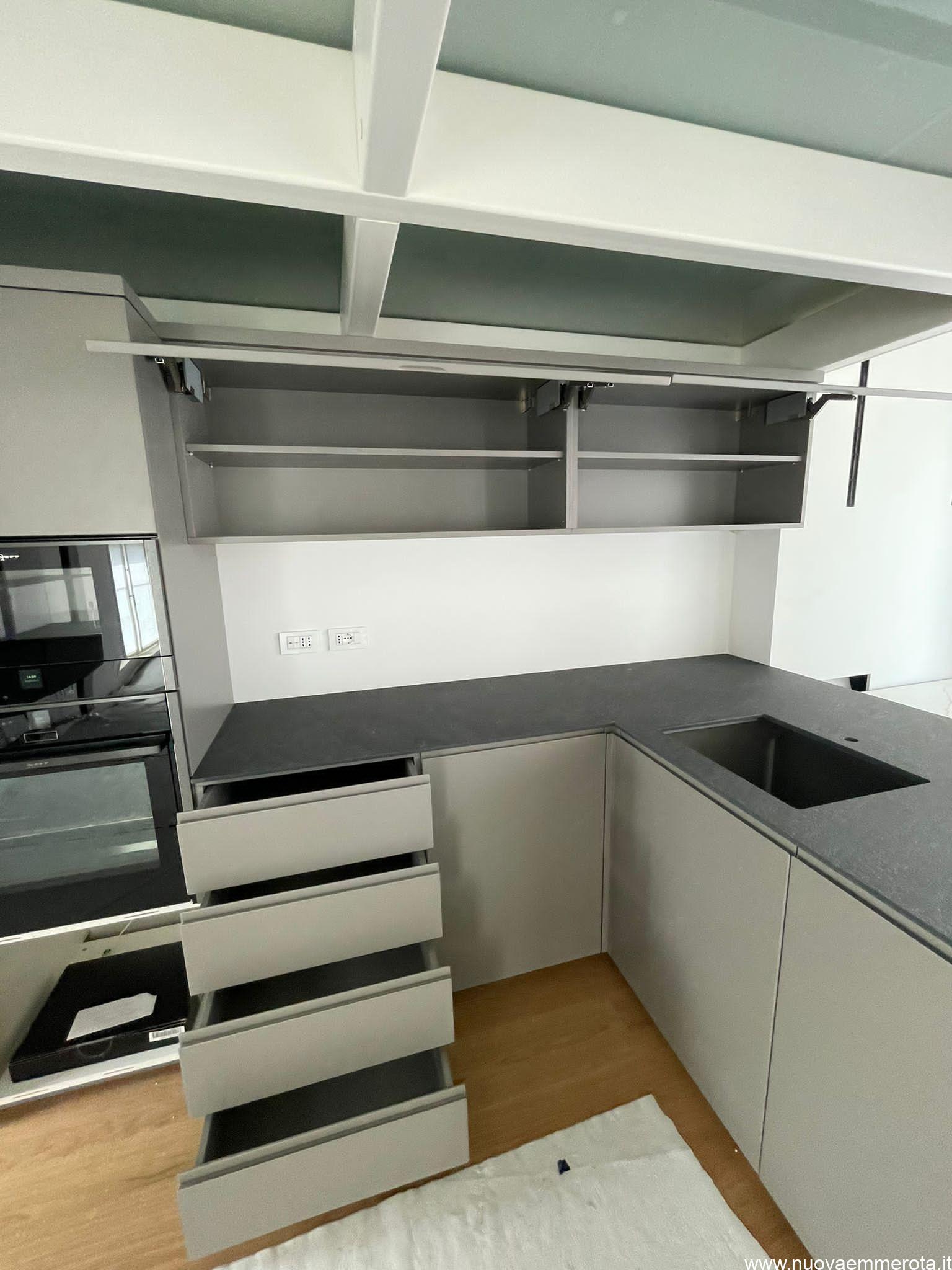 Cassetti e pensili aperti di una cucina su misura.