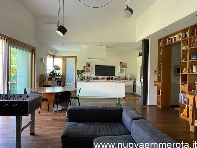 Open space con cucina ad isola, tavolo rotondo, libreria a parete, zona living.