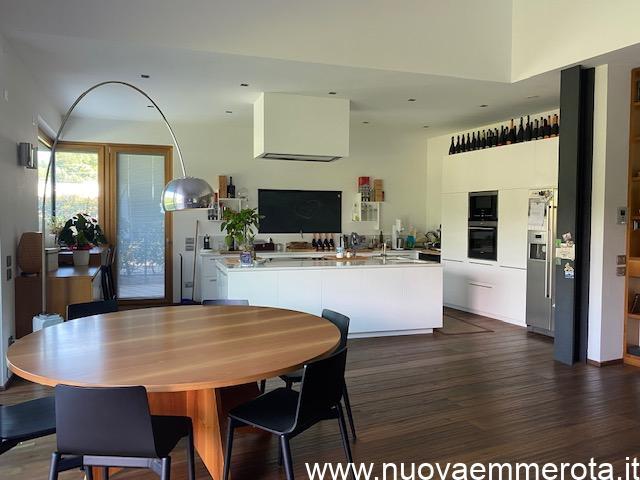 Open space con cucina ad isola zona living con tavolo rotondo in noce nazionale e sedie nere.