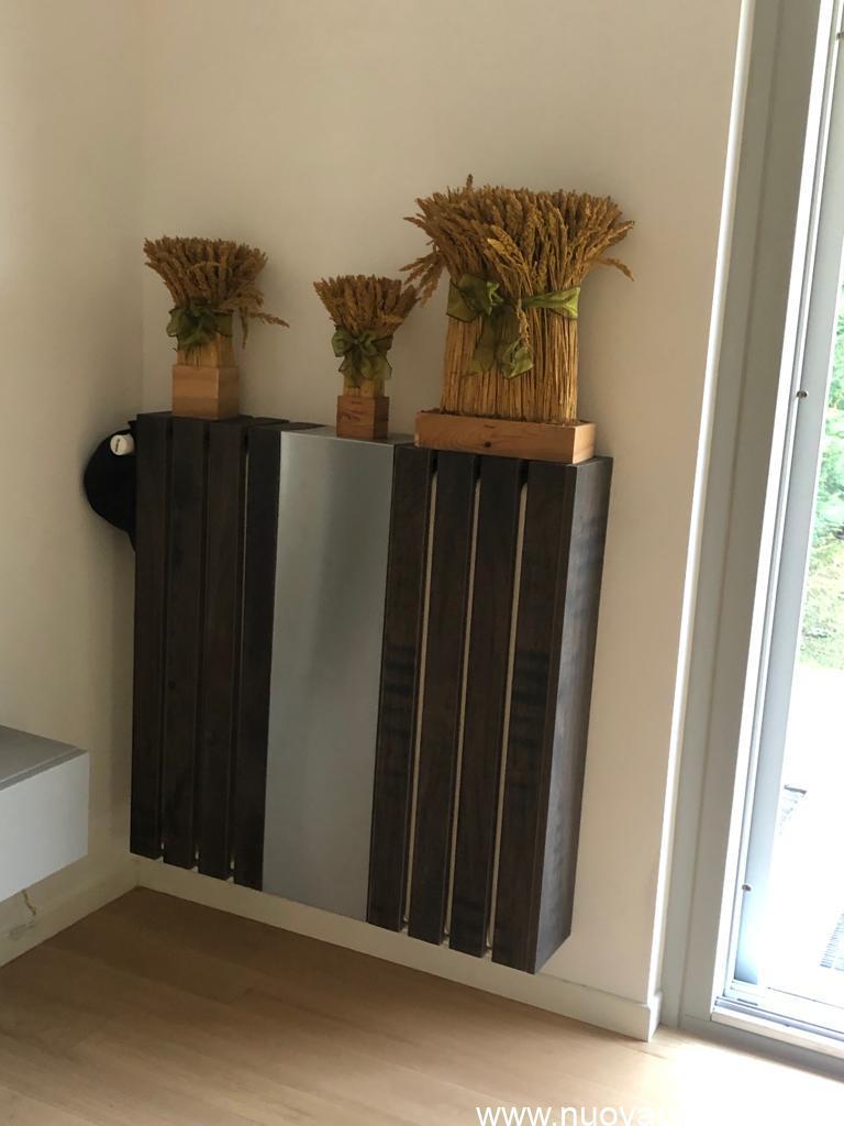 Listelli di legno e pannello in acciaio per copertura termosifone di design con decorazione.